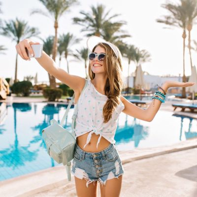 Graceful dancing girl in trendy bracelets and white hat making selfie before swimming in open-air pool. Gorgeous young woman with tanned skin in denim shorts and tank-top taking photo of herself